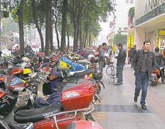 Scooters are parked by the hundreds on Chengdu sidewalks.