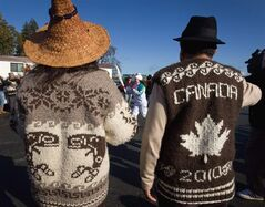 Amber Tommy (centre), 17, is framed by Cowichan First Nation Chief Lydia Hwitsum, left, and elder Albie Charlie, wearing traditional Cowichan sweaters, during the Vancouver 2010 Winter Olympic Games torch relay on Vancouver Island in Duncan, B.C., on Saturday October 31, 2009. The distinctive Cowichan sweater of B.C.'s Coast Salish First Nation has graced the bodies of people worldwide, and now it's being recognized by the Canadian government. THE CANADIAN PRESS/Darryl Dyck