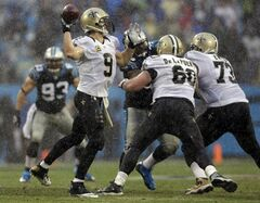 In the rain, New Orleans Saints' Drew Brees (9) looks to pass against the Carolina Panthers in the second half of an NFL football game in Charlotte, N.C., Sunday, Dec. 22, 2013. (AP Photo/Bob Leverone)