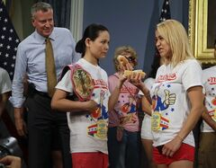 CORRECTS POSITION OF THOMAS AND SUDO- New York City Mayor Bill de Blasio watches hot dog eating contestants Sonya Thomas, left, and Miki Sudo, right, during a news conference to promote the upcoming Nathan's Famous Fourth of July Hot-Dog Eating Contest tomorrow Thursday, July 3, 2014, at City Hall in New York. (AP Photo/Frank Franklin II)