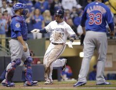 Milwaukee Brewers center fielder Carlos Gomez, center scores on a single by Jonathan Lucroy against the Chicago Cubs during the third inning of a baseball game Friday, April 25, 2014, in Milwaukee. (AP Photo/Darren Hauck)