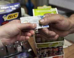 A consumer pays with a credit card at a store in Montreal on July 6, 2010. THE CANADIAN PRESS/Ryan Remiorz