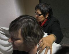 Delores Chief Abigosis, rear, a social worker testified again Tuesday at the Phoenix Sinclair Inquiry. Here her advocate tries to block her face while leaving the inquiry for a lunch break Monday.