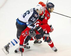 The Caps' Karl Alzner, (27) Dennis Wideman (6) block the Jets' Blake Wheeler.