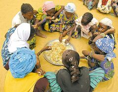 Students in Tagentassou, a Tuareg village, eat lunch provided as part of a school feeding program.