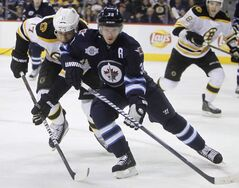 Boston Bruins' Milan Lucic (17) and Winnipeg Jets' Tobias Enstrom (39) battle for the puck during first-period NHL hockey action in Winnipeg, Friday.