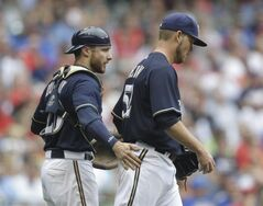 Milwaukee Brewers catcher Jonathan Lucroy encourages starting pitcher Jimmy Nelson as they walk back to the mound during the third inning of a baseball game against the St. Louis Cardinals Saturday, July 12, 2014, in Milwaukee. (AP Photo/Jeffrey Phelps)