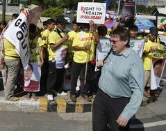 A foreign delegate walks past protesters to attend one of the world's largest tobacco trade shows dubbed ProTobEx ASIA at the World Trade Center at suburban Pasay city, south of Manila, Philippines Wednesday, March 20, 2013. The protesters assailed the tobacco manufacturers and other industry players allegedly for the smoking-related deaths of 240 Filipinos everyday. The World Health Organization has expressed concern that the Philippines is encouraging smoking by hosting one of the world's largest tobacco trade shows. (AP Photo/Bullit Marquez)