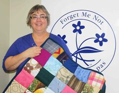 Trudy Mattey of the Alzheimer Society of Manitoba is seen holding a touch quilt.