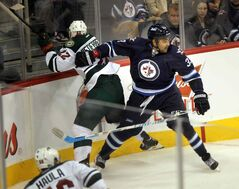 Winnipeg Jets defenceman Dustin Byfuglien keeps Nino Niederreiter of the Minnesota Wild out of the play during the first period of Thursday night's game at the MTS Centre.