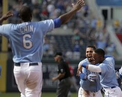 Kansas City Royals' Omar Infante, center, celebrates with Jarrod Dyson (1) and Lorenzo Cain (6) after hitting a game-winning single to score Alex Gordon during the ninth inning of a baseball game Sunday, June 29, 2014, in Kansas City, Mo. The Royals won 5-4. (AP Photo/Charlie Riedel)