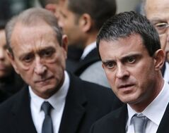 French Interior Minister Manuel Valls, right, talks to reporters after visiting Liberation newspaper, with Paris mayor Bertrand Delanoe, left, after a gunman opened fire in the lobby of Liberation newspaper in Paris, Monday, Nov.18, 2013. The gunman gravely injured an photographer's assistant before fleeing. Soon afterward, shots were fired at the headquarters of a major French bank just west of Paris, and a man had been taken hostage and a gunman forced his hostage to drive to the Champs-Elysees. (AP Photo/Thibault Camus)