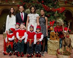 The first family, from left, Malia Obama, President Barack Obama, first lady Michelle Obama, and Sasha Obama, pose with children dressed like elves at the National Building Museum in Washington, Sunday, Dec. 15, 2013. The first family is attending the taping of the annual 2013 Christmas in Washington, celebrating its 32nd year anniversary. (AP Photo/Manuel Balce Ceneta)