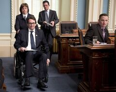 Quebec Opposition MNA Pierre Karl Peladeau leaves question period in a wheelchair Monday, May 26, 2014 at the legislature in Quebec City. Peladeau made his first appearance at the legislature since a major micycle accident that kept him out since he was elected. THE CANADIAN PRESS/Jacques Boissinot