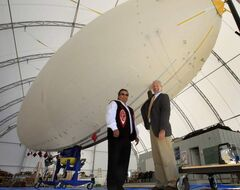 Grand Chief David Harper of Manitoba Keewatinowi Okimakanak (left) and Barry Prentice, president of ISOPolar, stand near a 70-foot unmanned airship in the BASI Airdock Airship Hangar at the  St. Andrews Airport.