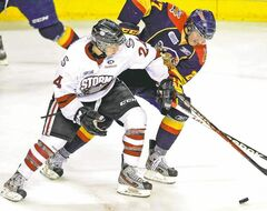 Guelph Storm's Scott Kosmachuk (left) scraps for the puck during OHL action.  Kosmachuk  was the Jets' third-round pick last summer.