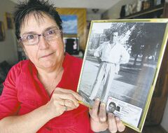 Debbie Scott holds a photo of her dad, who lost his Indian status because his Indian mother married a white man.