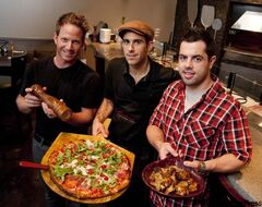 Carbone Coal Fired Pizza owners, from left, Sean Dollinger, Joseph Paletta (with pizza Peppino) and Daniel Simon (with chicken wings).