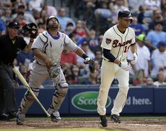 Atlanta Braves' Andrelton Simmons, right, tosses his bat after hitting a pop out as Colorado Rockies catcher Wilin Rosario, left, follows the ball in the fourth inning of a baseball game, Saturday, May 24, 2014, in Atlanta. (AP Photo/David Goldman)