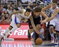 Los Angeles Clippers forward Matt Barnes, left, and Portland Trail Blazers center Robin Lopez, center, go after a loose ball along with forward Blake Griffin during the first half of an NBA basketball game, Wednesday, Feb. 12, 2014, in Los Angeles. (AP Photo/Mark J. Terrill)