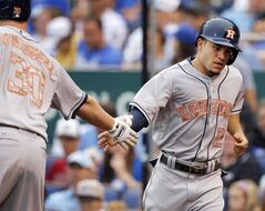 Houston Astros' Jose Altuve, right, is congratulated by teammate Matt Dominguez (30) after scoring during the first inning of a baseball game against the Kansas City Royals at Kauffman Stadium in Kansas City, Mo., Monday, May 26, 2014. (AP Photo/Orlin Wagner)