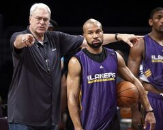 FILE - In this file photo from June 16, 2010, then Los Angeles Lakers coach Phil Jackson, left, directs Derek Fisher during NBA basketball practice in Los Angeles. The New York Knicks have scheduled a news conference for Tuesday, June 10, 2014, amid reports that Fisher has agreed to become the team's basketball head coach. (AP Photo/Reed Saxon)