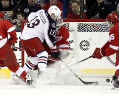 Columbus Blue Jackets' Cam Atkinson (13) scores past Detroit Red Wings goalie Jonas Gustavsson (50) of Swedenm and Niklas Kronwall (55) in the first period of an NHL hockey game in Columbus, Ohio, Saturday, March 9, 2013. (AP Photo/Paul Vernon)