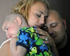 Christine Swidorsky holds her son, Logan Stevenson, 2, with her husband-to-be and Logan's father Sean Stevenson, for a portrait on Tuesday, July 30, 2013 in their Jeannette, Pa., home. The Pennsylvania couple plans to have their dying toddler serve as the groom's best man when they wed on Saturday, Aug. 3. The couple had planned to wed next year, but decided to move the ceremony up to Saturday so the boy, who has leukemia and other complications, could participate. Logan has Fanconi anemia, a rare disease that often results in cancer. Doctors last week gave the boy two to three weeks to live. (AP Photo/Tribune-Review, Eric Schmadel)