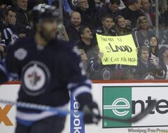 Fans hold signs Thursday giving their opinion on the franchise that used to belong in Winnipeg as the Winnipeg Jets host the Phoenix Coyotes at MTS Centre for the only time this season.