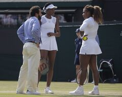 Umpire Kader Nouni talks to Serena Williams, right, and Venus Williams of the U.S during their women's doubles match against Kristina Barrios of Germany and Stefanie Voegele of Switzerland at the All England Lawn Tennis Championships in Wimbledon, London, Tuesday July 1, 2014. The Williams sisters retired after 3 games. (AP Photo/Pavel Golovkin)