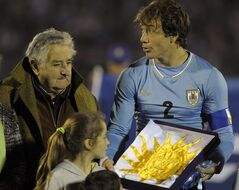 FILE - In this June 4, 2014, file photo, Uruguay's President Jose Mujica, left, gives Uruguay's captain Diego Lugano the national flag before an international friendly soccer match against Slovenia in Montevideo, Uruguay. Uruguay's famously casual President is tossing some earthy expletives at FIFA as he welcomed Uruguay's team back from the World Cup oon Sunday June 29, over its four-month ban of Luis Suarez. Uruguayans overwhelmingly criticized FIFA's decision to ban Suarez from nine national team games and four months for biting an Italian defender. (AP Photo/Matilde Campodonico, File)