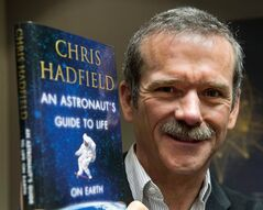 Retired Canadian astronaut Chris Hadfield holds a copy of his new book