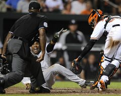 Chicago White Sox Alexi Ramirez reacts after being called safe at the plate by home plate umpire Alan Porter on a single by Alejandro De Aza as he eluded the tag from Baltimore Orioles catcher Caleb Joseph, right, in the eighth inning of a baseball game Tuesday, June 24, 2014, in Baltimore. The White Sox won 4-2. (AP Photo/Gail Burton)