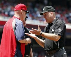 Washington Nationals manager Matt Williams, left, asks for a review from umpire Jeff Nelson, right, after Texas Rangers' Elvis Andrus was called safe at home during the first inning of a baseball game at Nationals Park, Sunday, June 1, 2014, in Washington. After the review, it was ruled that the runner did not score before the last out of the inning. (AP Photo/Alex Brandon)