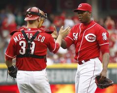 Cincinnati Reds relief pitcher Aroldis Chapman (54) is congratulated by catcher Devin Mesoraco (39) after the Reds defeated the Philadelphia Phillies 4-1 in a baseball game, Sunday, June 8, 2014, in Cincinnati. (AP Photo/David Kohl)