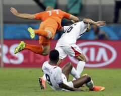 Netherlands' Arjen Robben falls over Costa Rica's Cristian Gamboa (16) after heading the ball during the World Cup quarterfinal soccer match at the Arena Fonte Nova in Salvador, Brazil, Saturday, July 5, 2014. (AP Photo/Natacha Pisarenko)