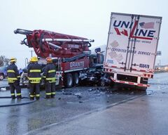 A pickup truck  jammed between a semi truck and cement truck caught fire.