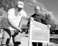 Lyle Misurn (left) helps Sam Katz plant a sign Saturday afternoon.