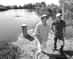 Bryan Oborne (left) and Les McEwan of the Tobacco Creek Model Watershed stand near a reservoir along the Tobacco Creek.