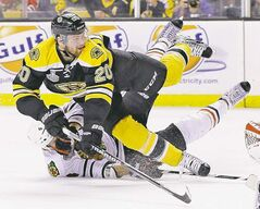 Bruins left-winger Daniel Paille -- who scored the other goal of the game -- is taken down by Blackhawks' Niklas Hjalmarsson in the second period.