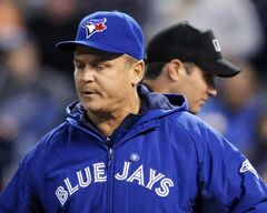Toronto Blue Jays manager John Gibbons returns to the dugout after questioning a call by umpire John Tumpane, back, during the sixth inning of a baseball game in Kansas City, Mo., Thursday, May 1, 2014. Gibbons has guided the Blue Jays to a perch atop the division standings THE CANADIAN PRESS/AP/Orlin Wagner