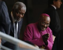 Retired Anglican Archbishop Desmond Tutu, right, arrives with Former U.N. Secretary-General Kofi Annan for the memorial service for former South African president Nelson Mandela at the FNB Stadium in the Johannesburg, South Africa township of Soweto, Tuesday Dec. 10, 2013. (AP Photo/Ben Curtis)