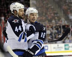 Winnipeg Jets defenceman Zach Bogosian (44) celebrates his goal with forward Bryan Little during the first period of an NHL game against the New Jersey Devils in Newark, N.J., Sunday.