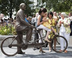Olivia Chow (centre right )looks on as Sarah Layton and her daughter Beatrice sit on a bronze statue of Jack Layton, the former NDP leader after it's unveiled at Toronto's ferry terminal on Thursday August 22, 2013. THE CANADIAN PRESS/Chris Young