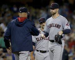 Cleveland Indians manager Terry Francona, left, takes starting pitcher Corey Kluber out during the seventh inning of a baseball game against the Los Angeles Dodgers in Los Angeles, Monday, June 30, 2014. (AP Photo/Chris Carlson)