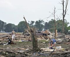 Jaime, right, and Jeff Hoadley, of Madison, Neb., look over the property next to her parents' home and St. John's Lutheran Church, where Jaime's father is pastor, in Pilger, Neb., after tornadoes moved through the area Monday, June 16, 2014. A storm packing rare dual tornadoes tore through the tiny farming town in northeast Nebraska, killing a 5-year-old girl, leaving grain bins crumpled like discarded soda cans and flattening dozens of homes. (AP Photo/The Norfolk Daily News, Darin Epperly)