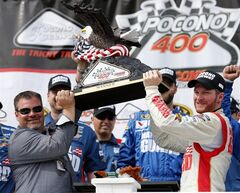 Dale Earnhardt Jr., right, holds the winner's trophy with Pocono Raceway President Brandon Igdalsky after the NASCAR Sprint Cup Series Pocono 400 auto race at Pocono Raceway on Sunday, June 8, 2014, in Long Pond, Pa. (AP Photo/Mike Groll)