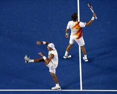 Lukasz Kubot of Poland, left, and Robert Lindstedt of Sweden celebrate after defeating Eric Butorac of the U.S. and Raven Klaasen of South Africa in their men's doubles final at the Australian Open tennis championship in Melbourne, Australia, Saturday, Jan. 25, 2014.(AP Photo/Eugene Hoshiko)