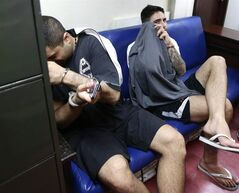 Arrested Canadian nationals James Clayton Riach, right, and Ali Memar Mortazavi Shirazi wait for their inquest proceeding at the Department of Justice in Manila, Philippines, Thursday, Jan. 16, 2014. THE CANADIAN PRESS/AP, Bullit Marquez