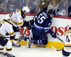 Jets' centre Mark Scheifele does a header into the boards after being hammered by Boston's Kevan Miller in the first period.